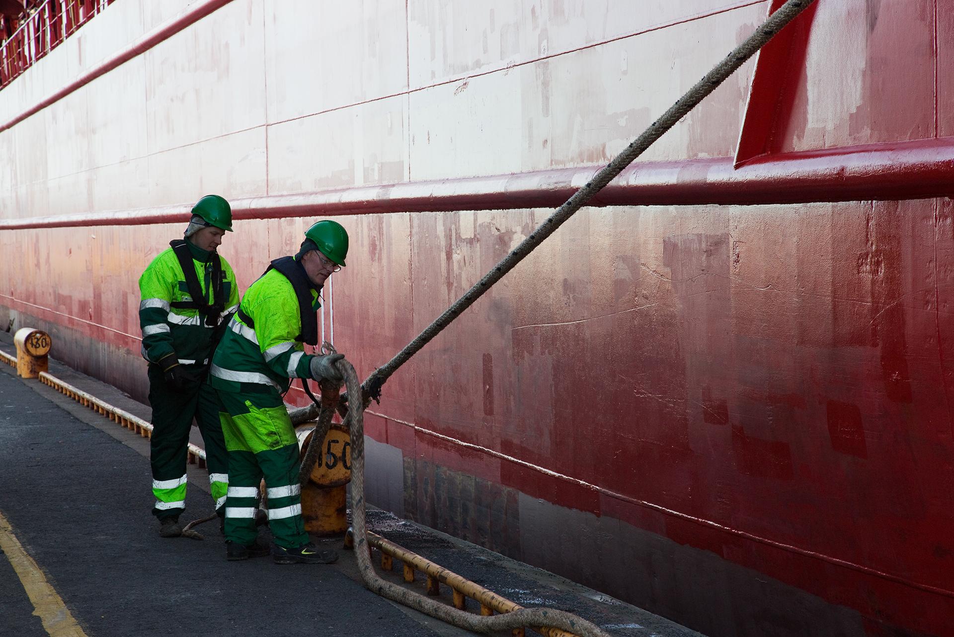 Satamavalvojat irrottamassa laivan köysiä, jotta laiva pääsee jatkamaan matkaa seuraavaan satamaan.